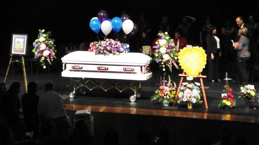 The casket of 11-year-old Ashlynne Mike sits in the center of the stage, surrounded by bouquets of flowers, at Farmington Civic Center in Farminton, N.M. before her memorial service Friday, May 6, 2016. Hundreds of mourners turned out for the service.  The FBI said Ashlynne Mike, was abducted after school on Monday and her body was found the next day.  Tom Begaye was arrested in connection with Mike's disappearance and death. (AP Photo/Susan Montoya Bryan)