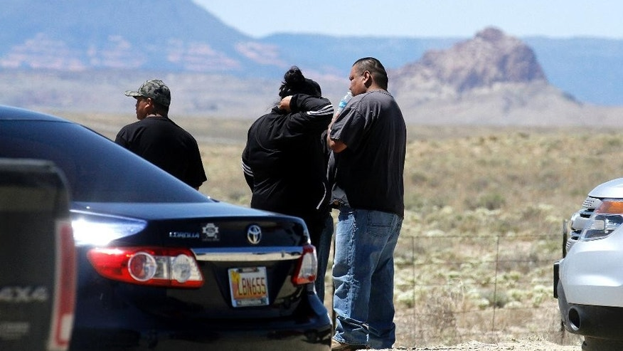 Family and friends gather along Navajo Route 13, just a few miles from where Ashlynne Mike's body was discovered, in south of Shiprock, N.M., on Tuesday, May 3, 2016. Police gleaned some information about the suspect from the younger brother of Ashlynne, whose body was found Tuesday near a distinct rock formation that the rural town of Shiprock, N.M., is named for. Authorities are poring over parts of the Navajo Nation in search of the man who snatched the children and killed Ashlynne. (Jon Austria/The Daily Times via AP) MANDATORY CREDIT