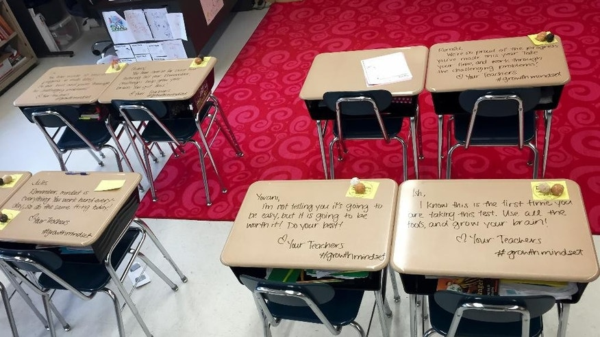This Monday, May 2, 2016 photo provided by Crystal Ramirez shows student desks in Chandni Langford's 5th grade classroom, in Woodbury, N.J.  Langford wrote inspirational messages directly on her students' desks on Monday before they started four days of high-pressure, high-stakes Common Core-aligned tests. (Crystal Ramirez via AP)