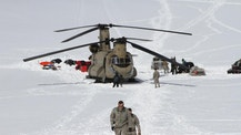 This photo taken Sunday, April 24, 2016, on the Kahiltna Glacier in Alaska, shows Capt. Corey Wheeler, front, commander of B Company, 1st Battalion, 52nd Aviation Regiment at Fort Wainwright, Alaska, walking away from a Chinook helicopter that landed on the glacier near Denali. The U.S. Army helped set up base camp on North America's tallest mountain. Three Chinook helicopters the size of city buses took supplies like food, communication equipment and fuel to the base camp at the 7,200-foot level of Denali.  (AP Photo/Mark Thiessen)