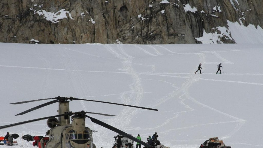 This photo taken Sunday, April 24, 2016, on the Kahiltna Glacier in Alaska, shows Army soldiers unloading a Chinook helicopter that landed on the glacier near Denali. The U.S. Army helped set up base camp on North America's tallest mountain. Three Chinook helicopters the size of city buses took supplies like food, communication equipment and fuel to the base camp at the 7,200-foot level of Denali.  (AP Photo/Mark Thiessen)