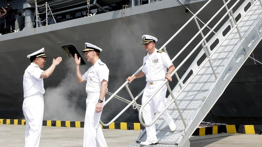 Vice Admiral Joseph P. Aucoin, commander of the U.S. Navy's 7th fleet, center, shakes hands with Chinese People's Liberation Army (PLA) Navy Rear Admiral Zhi Tianlong, left, during a visit by USS Blue Ridge at a port in Shanghai, Friday, May 6, 2016. The commander of the U.S. Navy's 7th Fleet has dismissed the cancellation of a planned port visit to Hong Kong by an American aircraft carrier as a minor hurdle in relations between the two militaries. (AP Photo)