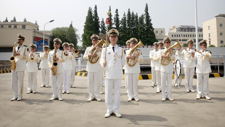 A Chinese People's Liberation Army (PLA) Navy band plays as the USS Blue Ridge arrives at a port in Shanghai, Friday, May 6, 2016. The commander of the U.S. Navy's 7th Fleet has dismissed the cancellation of a planned port visit to Hong Kong by an American aircraft carrier as a minor hurdle in relations between the two militaries. (AP Photo)