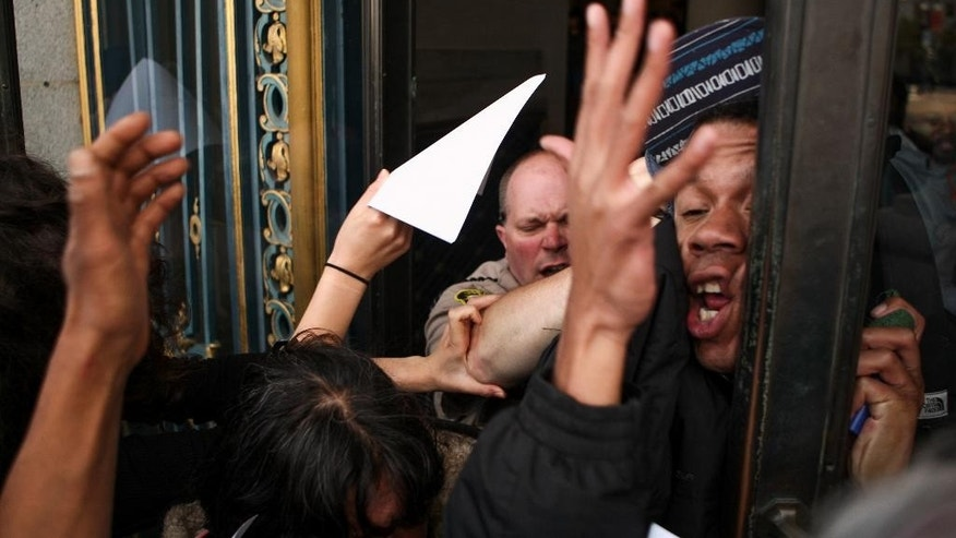 James Burch gets slammed by a San Francisco deputy sheriff, after protestors stormed through the east side entrance of City Hall on Friday, May 6, 2016. Protesters entered the building after doors were locked blocking off the public from entering the building during a protest against SFPD and in support of the Frisco 5 hunger strikers in San Francisco. (AP Photo/Joel Angel Juarez)