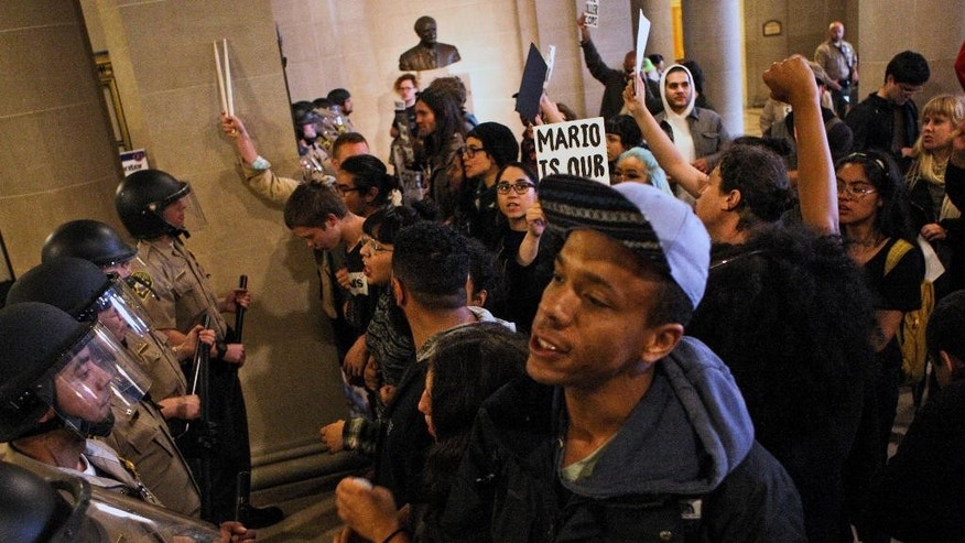 Protesters face off with San Francisco deputy sheriffs, after they stormed through the east side entrance of City Hall on Friday, May 6, 2016. Protesters entered the building after doors were locked blocking off the public from entering the building during a protest against SFPD and in support of the Frisco 5 hunger strikers in San Francisco. (AP Photo/Joel Angel Juarez)