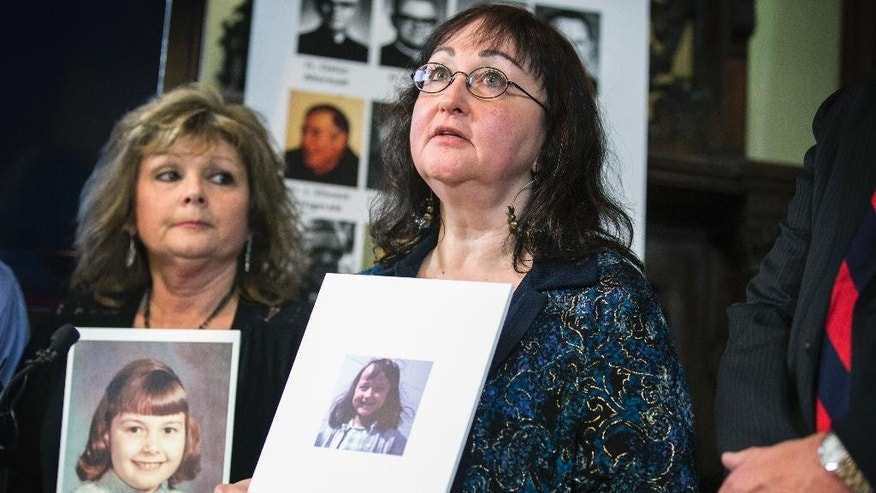 In this March 29, 2016, photo, Lori Stoltz, one of the victims of deceased Diocese of New Ulm priest, the Rev. David Roney, holds a photo of herself at the age when she was abused as she speaks during a press conference in St. Paul, Minn. It's been nearly three years since Minnesota opened a path for lawsuits by alleged victims of long-ago childhood sexual abuse. That window closes May 25, but the impact has been huge. Hundreds of people have come forward against churches, the Boy Scouts, schools and other institutions. (Leila Navidi/Star Tribune via AP) MANDATORY CREDIT; ST. PAUL PIONEER PRESS OUT; MAGS OUT; TWIN CITIES LOCAL TELEVISION OUT   TV is soft out