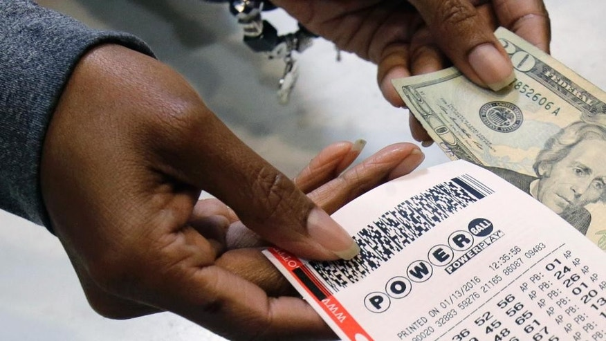 FILE - In this Jan. 13, 2016 file photo, a clerk hands over a Powerball ticket for cash at Tower City Lottery Stop in Cleveland. Powerball estimates that its jackpot for the May 4, 2016, drawing is $348 million. (AP Photo/Tony Dejak, File)