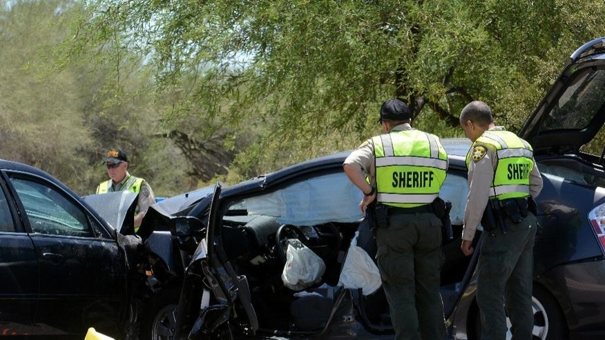 May 7, 2016: Pima County Sheriff's Department deputies examine a wrecked Toyota Prius at the scene of a fatal car crash on East Ina Road west of Westward Look Drive north of Tucson, Ariz.