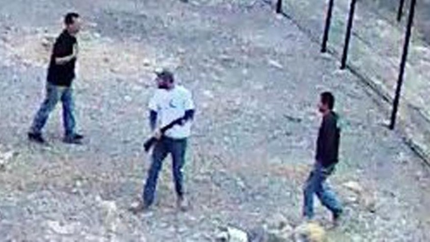 In this still image taken from security video on Saturday, April 30, 2016 and released by the National Park Service, three men inside the perimeter fence at the edge of Devils Hole in Death Valley National Park, Nev. Authorities on Monday were searching for the three men who went on a drunken binge in an environmentally fragile area of Death Valley National Park, leaving behind beer cans, shotgun shells, vomit, underwear — and possibly killing one of the rarest fishes on earth, a Devils Hole pupfish. (National Park Service via AP)