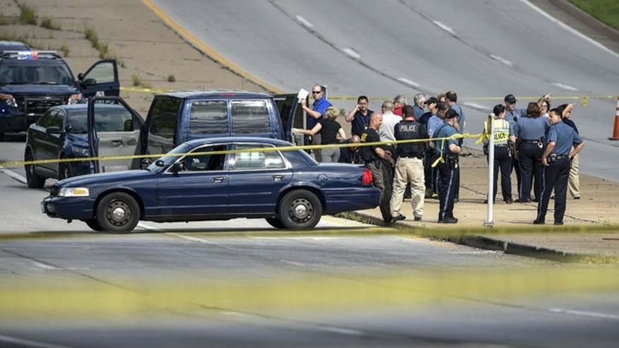 Authorities talk after they closed both directions of Bannister Road along with both directions of Highway 71 in their investigation of a carjacking and shooting suspect arrest Monday, May 9, 2016, in Kansas City, Mo. (David Eulitt /The Kansas City Star via AP) MANDATORY CREDIT