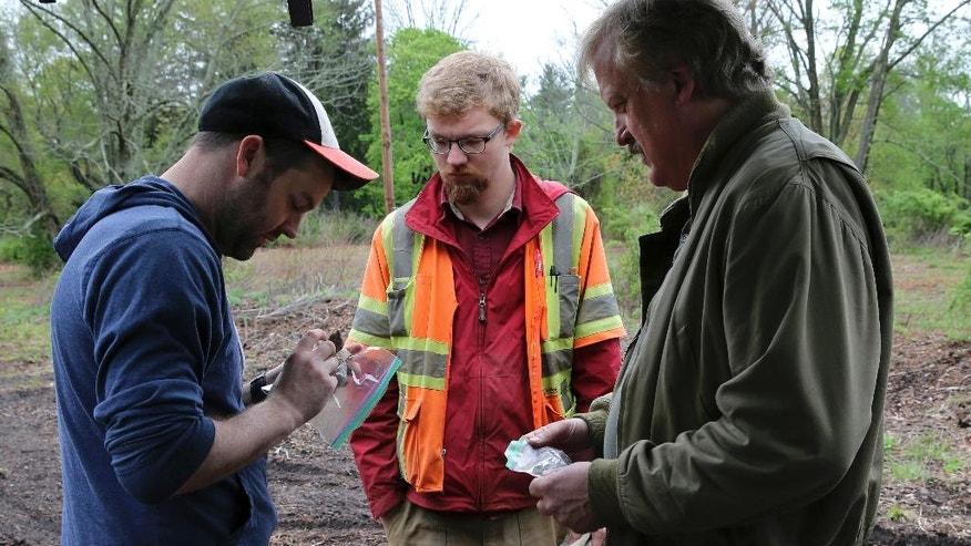 In this May 5, 2016, photo, Kevin Bradley, left, and Donald Purdon, project archeologists with Commonwealth Heritage Group, a Michigan-based firm that specializes in archaeological surveying, look at some items found by William Styple, right, at a site in Chatham, N.J. (AP Photo/Mel Evans)