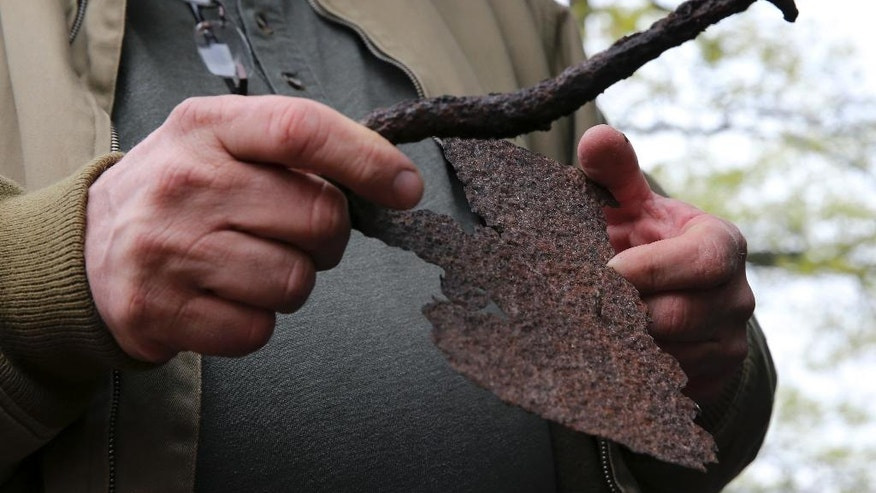 In this May 5, 2016, photo, William Styple holds an old farm implement that he unearthed while looking for artifacts in Chatham, N.J. A group is digging for artifacts that may be the best evidence yet, that this unspoiled swath of land about 15 miles west of Newark Liberty International Airport hosted Gen. George Washington's army in the winter of 1777, a year before the ragtag group hunkered down at its more well-known refuge at Valley Forge, Pa. (AP Photo/Mel Evans)