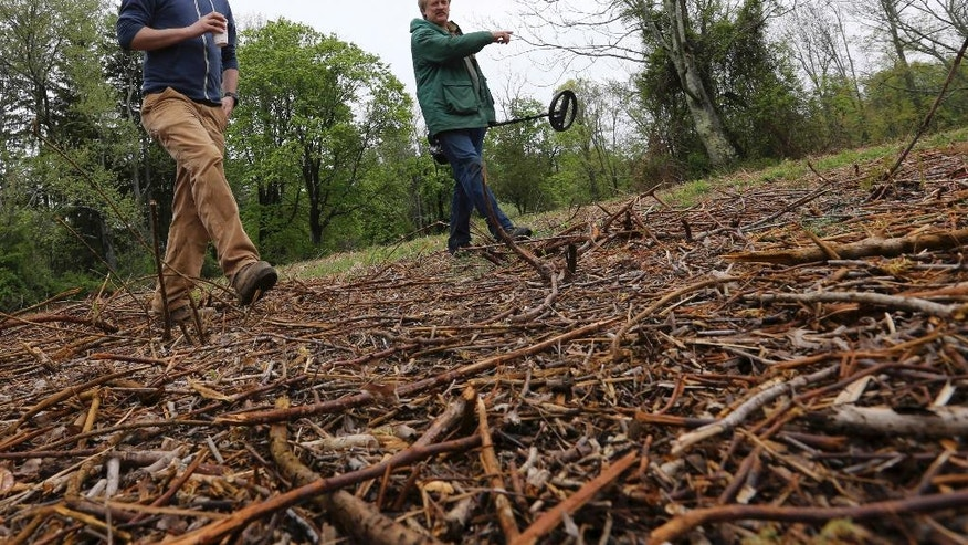 In this Thursday, May 5, 2016, photo, William Styple, right, carries a metal detector as he walks with project archeologist Kevin Bradley, of Commonwealth Heritage Group, a Michigan-based firm that specializes in archaeological surveying, as they look for artifacts in Chatham, N.J. Archaeologists have uncovered artifacts from a site in northern New Jersey where American soldiers likely camped during the early part of the Revolutionary War. (AP Photo/Mel Evans)