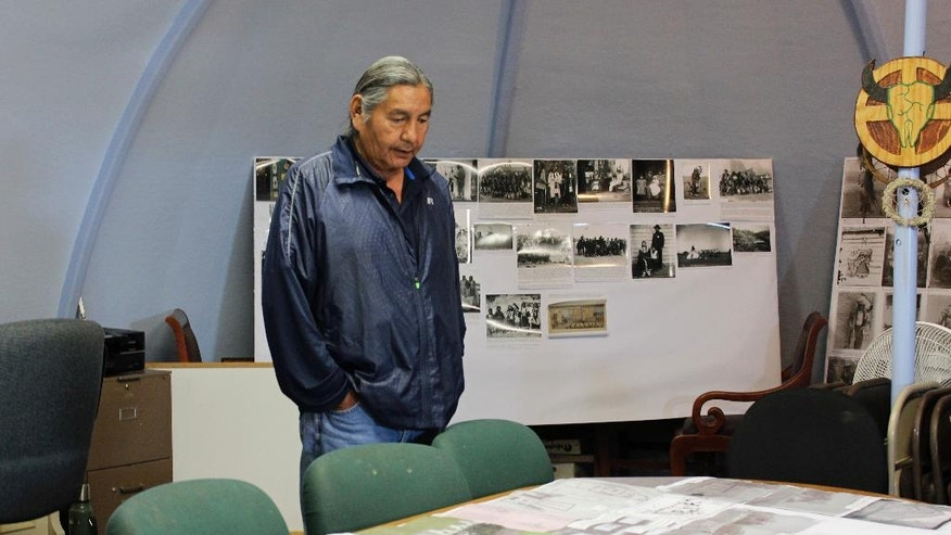 In this May 6, 2016, photo, Russell Eagle Bear, the historic preservation officer for the Rosebud Sioux Tribe, looks at photos and maps in his office in Rosebud, S.D., of the Carlisle Indian Industrial School in Pennsylvania. Eagle Bear will be leading a meeting Tuesday, May 10 between leaders of several tribes, including the Rosebud Sioux Tribe, and representatives from the U.S. Army to address the possibility of repatriating the remains of at least 10 Native American children who died away from their homes while being forced to attend the school more than a century ago. (AP Photo/Regina Garcia Cano)