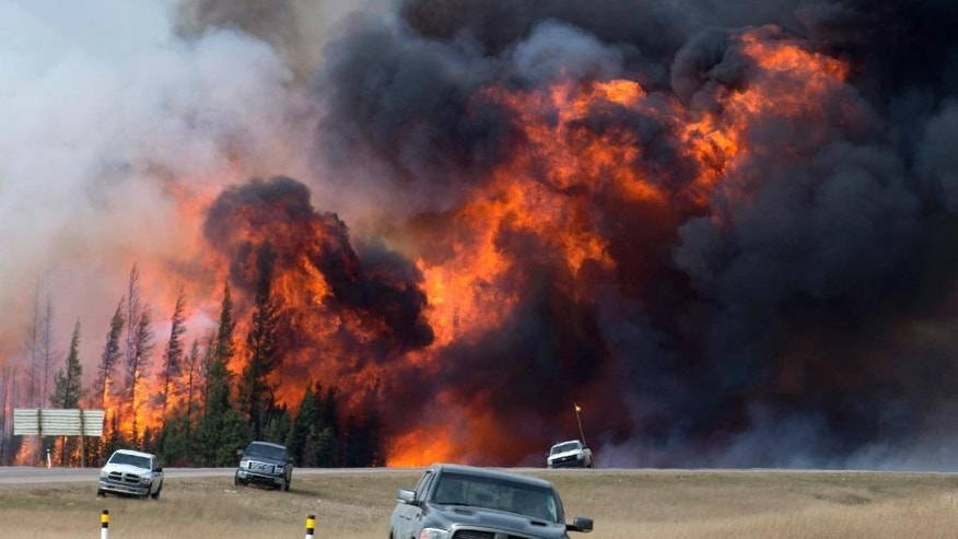 FILE - In this May 7, 2016 file photo, a wildfire burns south of Fort McMurray, Alberta. A dry and blistering hot northern Alberta is burning and doing so unusually early in the year, but that's only the latest of many gargantuan fires on an Earth that's grown hotter with more extreme weather.  (Jonathan Hayward /The Canadian Press via AP, File) MANDATORY CREDIT