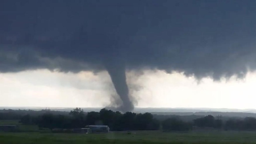 """This image made from a video taken through a car window shows a tornado near Wynnewood, Okla., Monday, May 9, 2016. A broad tornado capable of leaving """"catastrophic"""" damage in its wake churned across the Oklahoma landscape Monday, prompting forecasters to declare a tornado emergency for two communities directly in its path. (Hayden Mahan via AP) MANDATORY CREDIT"""