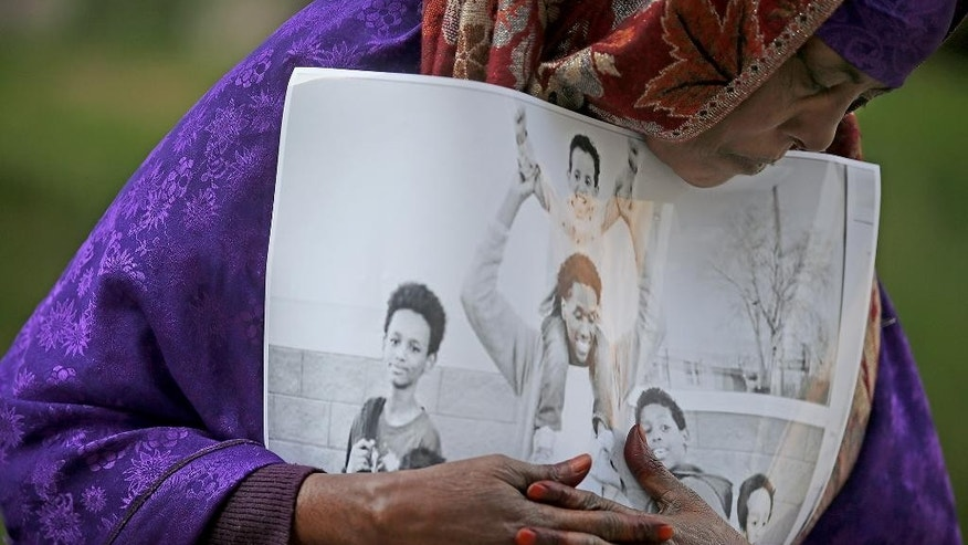 Haqhawo Qaasim holds onto a photo of Guled Ali Omar, who is scheduled to stand trial Monday, while standing in front of the United States Courthouse, Monday, May 9, 2016 in Minneapolis. Omar is one of three defendants who have pleaded not guilty to conspiring to provide material support to the Islamic State group. (Elizabeth Flores/Star Tribune via AP) MANDATORY CREDIT