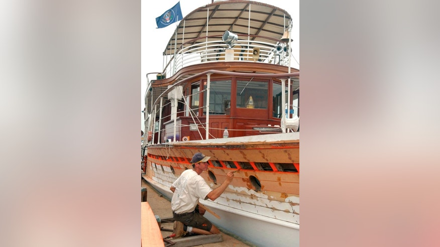FILE- In this Aug. 13, 2003, file photo, Chesapeake Maritime Museum Shipwright apprentice Bob Savage greases the adjacent planks before fitting additional pieces into place during renovations to the yacht Sequoia in St. Michaels, Md. A Delaware judge is holding a hearing Wednesday, May 11, 2016, to determine a price at which a lender can exercise an option to purchase the former presidential yacht Sequoia or cede possession to its current owners. (AP Photo/Don Wright, File)