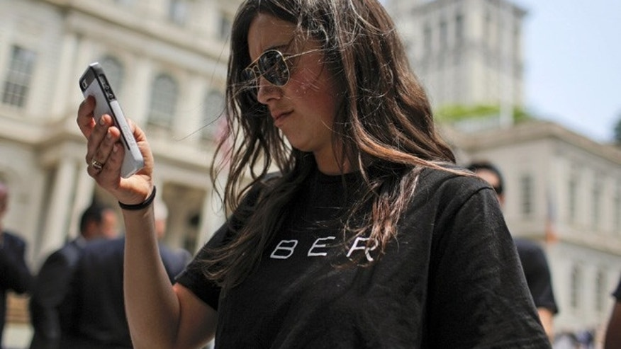 FILE: A woman wearing a Uber T-shirt checks her phone while Uber riders and driver-partners take part in a rally on the steps of New York City Hall.
