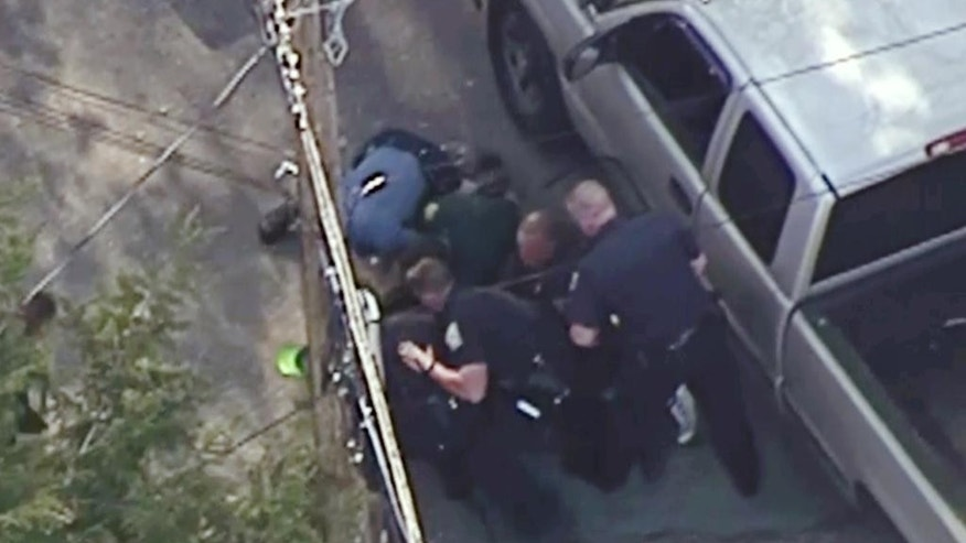 This aerial image made from a helicopter video provided by WHDH shows several officers pummeling Richard Simone, who had exited his vehicle and kneeled on the ground after a high-speed police pursuit, in Nashua, N.H., Wednesday, May 11, 2016. The chase went through several towns before ending in Nashua. (Courtesy WHDH via AP) MANDATORY CREDIT; BOSTON OUT