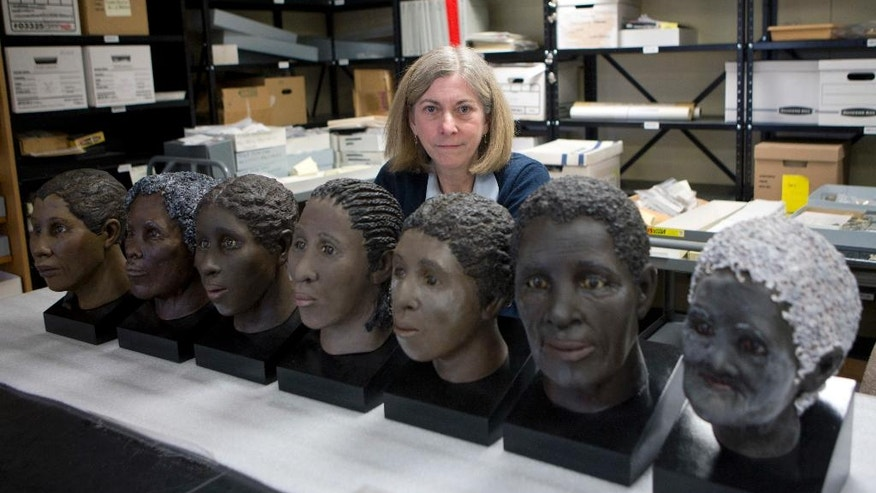 In this April 27, 2016 photo, Lisa Anderson, curator of bioarchaeology at the New York State Museum, poses in Albany, N.Y., with facial reconstructions of slaves found at an unmarked cemetery. The reconstructions were done by the museum. Fourteen slaves will be buried a second time, a decade after construction workers accidentally uncovered their remains north of Albany. (AP Photo/Mike Groll)