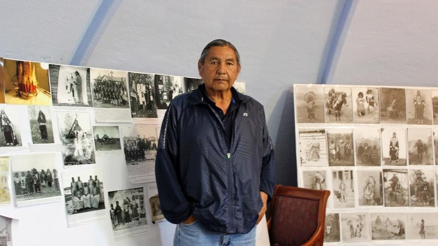 In this May 6, 2016, file photo, Russell Eagle Bear, the historic preservation officer for the Rosebud Sioux Tribe, stands in his office in in Rosebud, S.D. A group of tribes pushing to place Pe' Sla, a site that's sacred to the Great Sioux Nation, into a federal trust has come up against the state of South Dakota. The state in April appealed a federal decision to take the land purchased by the tribes into trust. (AP Photo/Regina Garcia Cano, File)