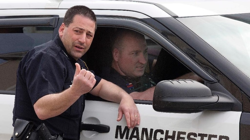 Police speak to each other as the search continues for a suspect who shot two police officers overnight Friday, May 13, 2016, in Manchester, N.H.  Authorities say the officers were shot early in the morning and are recovering at hospitals. (AP Photo/Jim Cole)