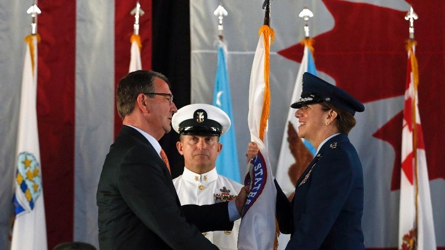 U.S. Defense Secretary Ash Carter, left, hands the U.S. Northern Command flag to Air Force Gen. Lori J. Robinson, the incoming commander of the North American Aerospace Defense Command and U.S. Northern Command, during the change of command ceremony at Peterson Air Force Base, in Colorado Springs, Colo., Friday, May 13, 2016. Gen. Robinson is the first woman to lead a top-tier U.S. military command after taking charge Friday at NORAD and USNORTHCOM. (AP Photo/Brennan Linsley)