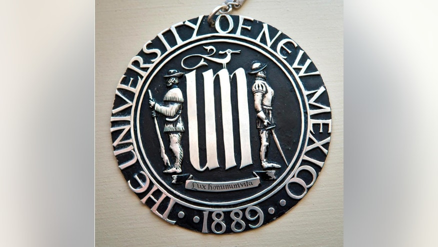 This undated photo shows the University of New Mexico's official seal, depicting a Spanish conquistador and a frontiersman, that is drawing accusations of racism from Native American students. New Mexico's largest university is considering revising its half-century old seal over concerns by Native American students who say it represents the frontier's violent era.  (Marla Brose/Albuquerque Journal via AP