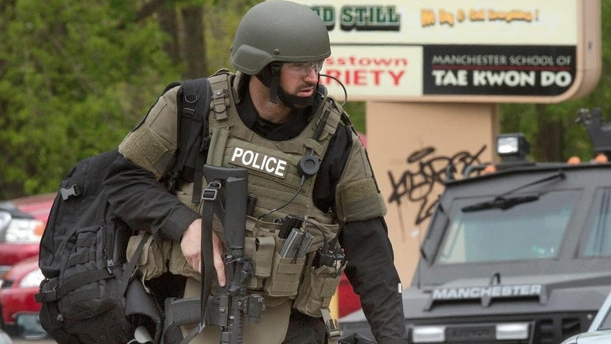 A police officer works the scene Friday, May 13, 2016, in Manchester, N.H., after two police officers were shot overnight. No immediate details on the shootings were available. (AP Photo/Jim Cole)