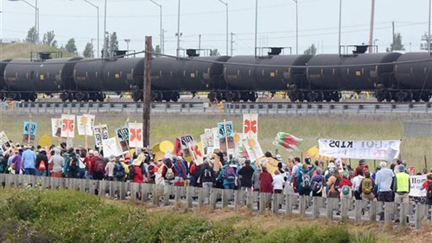 "Anti-oil protestors walk past the Tesoro refinery rail yard in Anacortes, Wash., on Saturday, May 14, 2016. The protests are part of a series of global actions calling on people to ""break free"" from dependence on fossil fuels. (Scott Terrell/Skagit Valley Herald via AP)"