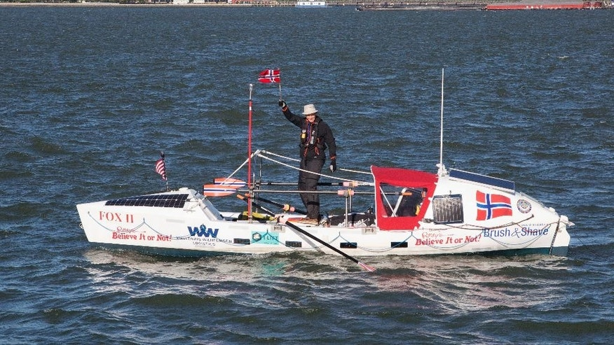 Stein Hoff, 70, waves a Norwegian flag as he passes Ellis Island, top left, Sunday, May 15, 2016 in New York. He is attempting to row singlehandedly across the Atlantic to England, a trip he predicts will take 3 months. Hoff is recreating the 1896 journey of two Norwegian-Americans, George Harbo and Gabriel Samuelsen _ the first people to row across an ocean. (AP Photo/Mark Lennihan)