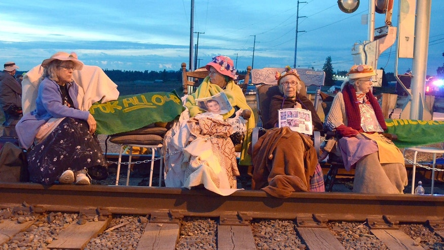 Members of the Seattle Raging Grannies sit in their rocking chairs chained together on the Burlington-Northern Railroad tracks at Farm to Market Road in Skagit County on Friday evening, May 13, 2016, in Burlington, Wash.