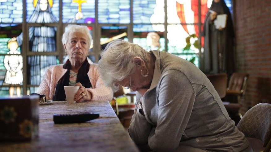 Mary Fernandes, left, and Nancy Shilts, right, and other parishioners at the church of St. Frances X. Cabrini react in the church Monday, May 16, 2016, while talking about its closing in Scituate, Mass. The Supreme Court has refused to hear an appeal from parishioners who are occupying the church, which the Roman Catholic Archdiocese of Boston closed more than a decade ago. (AP Photo/Steven Senne)