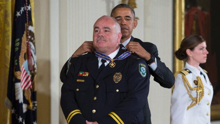President Barack Obama presents the Medal of Valor to Midwest City, Okla. Police Major David Huff.