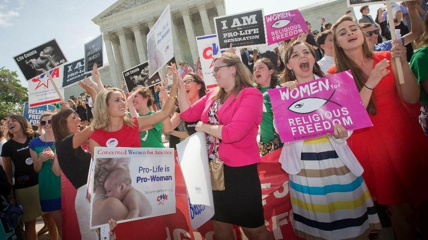 FILE - In this June 30, 2014 file photo, demonstrators react to hearing the Supreme Court's decision on the Hobby Lobby birth control case outside the Supreme Court in Washington. The Supreme Court rid itself Monday, May 16, 2016, of a knotty dispute between faith-based groups and the Obama administration over birth control. The court asked lower courts to take another look at the issue in a search for a compromise. (AP Photo/Pablo Martinez Monsivais, File)