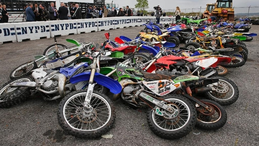 A pile of 70 confiscated motorcycles and all-terrain vehicles are on display after the New York Police Department crushed some of the 700 confiscated vehicles at the Erie Basin tow pound in Brooklyn's Red Hook neighborhood Tuesday, May 17, 2016, in New York. New York Police Department Commissioner William Bratton, who attended the event, said the department has been cracking down on unlicensed drivers who operate ATVs, mini-bikes and motorcycles without helmets. So far this year, more than 679 bikes have been confiscated and dozens of drivers arrested on such charges as reckless endangerment. (AP Photo/Kathy Willens)