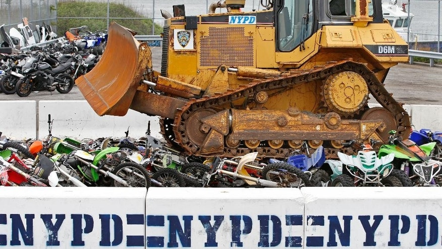 A driver rides a bulldozer atop 70 confiscated motorcycles and all-terrain vehicles as the New York Police Department crushed some of the confiscated bikes stored at the Erie Basin tow pound Brooklyn's Red Hook neighborhood, Tuesday, May 17, 2016, in New York. New York City Police Commissioner William Bratton said the department has been cracking down on unlicensed drivers who operate ATVs, mini-bikes and motorcycles without helmets. So far this year, more than 679 bikes have been confiscated and dozens of drivers arrested on such charges as reckless endangerment. (AP Photo/Kathy Willens)