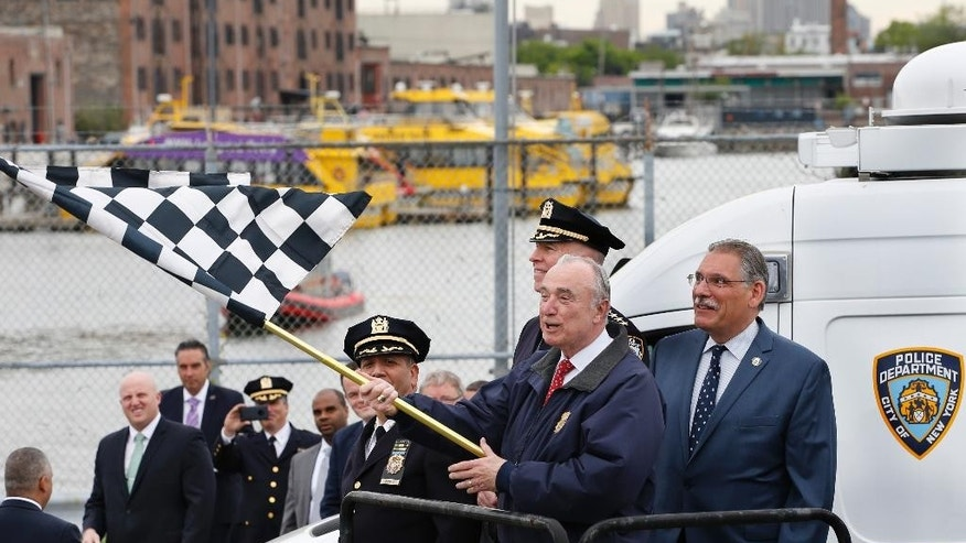 New York City Police Commissioner William Bratton waves a checked flag to signal the start of the crushing of 70 confiscated motorcycles and all-terrain vehicles at the Erie Basin tow pound Brooklyn's Red Hook neighborhood Tuesday, May 17, 2016, in New York. Bratton said the police department has been cracking down on unlicensed drivers who operate ATVs, mini-bikes and motorcycles without helmets.   (AP Photo/Kathy Willens)
