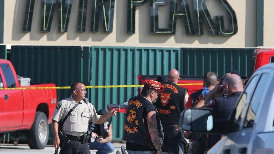 FILE - In this May 17, 2015, file photo, authorities investigate a shooting in the parking lot of the Twin Peaks restaurant in Waco, Texas. An attorney for one of the nearly 200 bikers arrested after a shooting melee outside the Waco, Texas, restaurant last year that left nine dead filed a motion Tuesday, May 17, 2016,  seeking to disqualify the district attorney and others from participating in any of the pending cases. (AP Photo/Jerry Larson, File)