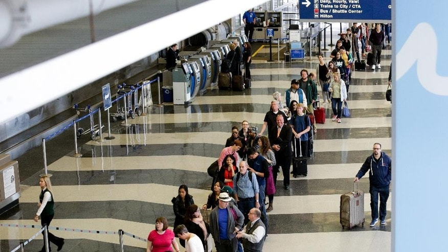 A long line of travelers wait for the TSA security check point at O'Hare International airport, Monday, May 16, 2016, in Chicago. Already faced with lines that snake through terminals out to the curb, fliers are bracing for long waits at security in the busy months of July and August. Some major airports are currently seeing wait times exceeding 90 minutes at peak hours. (AP Photo/Teresa Crawford)