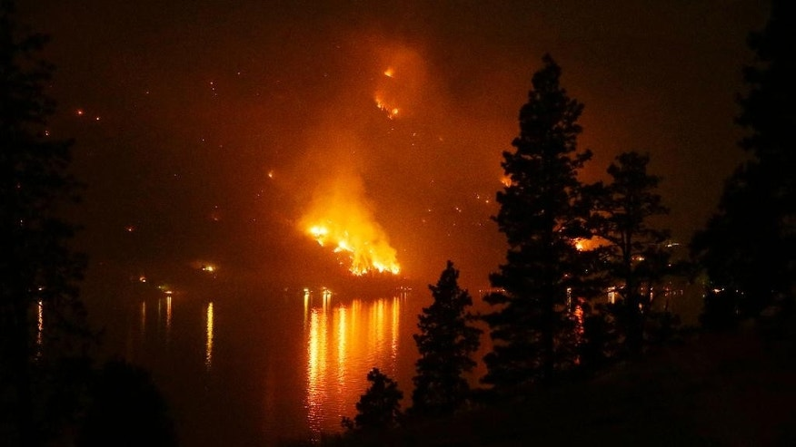 FILE - In this Aug. 17, 2015 file photo, timber burns in the First Creek fire near lakeside structures on the western shore of Lake Chelan near Chelan, Wash. The nation's primary wildfire-fighters are getting ready for the 2016 season, which is expected to be worse than average in Hawaii, Alaska and the Southwest. U.S. Forest Service Chief Tom Tidwell and Agriculture Secretary Tom Vilsack will meet with regional forest officials Tuesday, May 17, 2016, to discuss plans and preparations.  (AP Photo/Ted S. Warren, File)