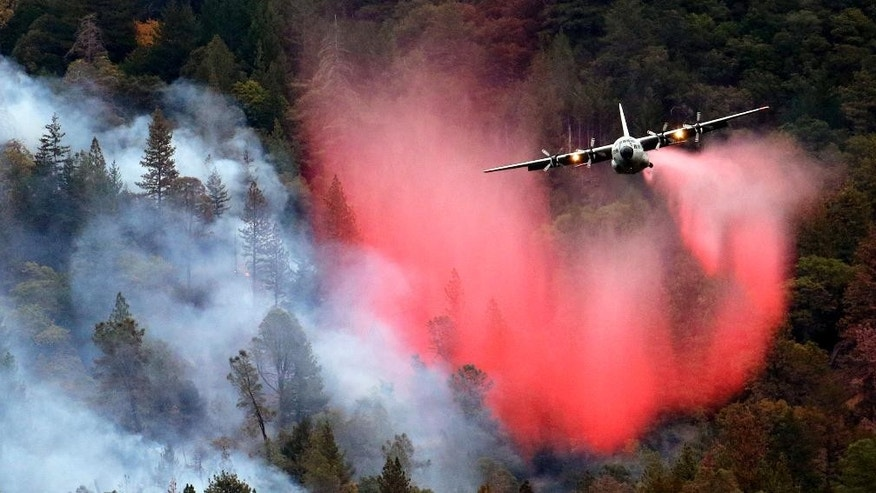 File - In this Sept. 15, 2015 file photo, a firefighting plane drops a load of fire retardant over a smoldering hillside, in Middletown, Calif. The nation's primary wildfire-fighters are getting ready for the 2016 season, which is expected to be worse than average in Hawaii, Alaska and the Southwest. U.S. Forest Service Chief Tom Tidwell and Agriculture Secretary Tom Vilsack will meet with regional forest officials Tuesday, May 17, 2016, to discuss plans and preparations.  (AP Photo/Elaine Thompson, File)