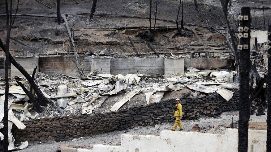 File - In this Sept. 15, 2015 file photo, firefighter Jeff Ohs walks below a scorched hillside and buildings at the Harbin Hot Springs resort, ravaged in a wildfire several days earlier, near Middletown, Calif. The nation's primary wildfire-fighters are getting ready for the 2016 season, which top forest officials say is expected to be worse than average in Hawaii, Alaska and the Southwest. In 2015, wildfires burned a record 15,800 square miles nationwide, with seven Forest Service firefighters losing their lives in the line of duty. (AP Photo/Elaine Thompson, File)