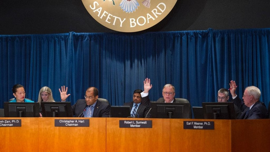Members of the National Transportation Safety Board (NTSB) votes on a motion to adopt an explanation for the derailment of an Amtrak passenger train that derailed in Philadelphia last year, Tuesday, May 17, 2016, during their board meeting in Washington. Board members, from left are; T. Bella Dihn-Zarr, Ph.D. vice chair, Christopher Hart, chairman, Robert Sumwalt, member, and Earl Weener, Ph.D., member. (AP Photo/Cliff Owen)