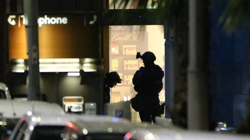 "FILE - In this Dec. 16, 2014 file photo, armed tactical response officers stand ready to enter the Lindt cafe during a siege in the central business district of Sydney, Australia. Five years before he held 18 people hostage inside a Sydney cafe where he ultimately died in a gun battle with police, Iranian-born Man Haron Monis attracted the attention of the FBI as someone who had ""the potential to incite others to violence,"" according to documents obtained by The Associated Press.  (AP Photo/Glenn Nicholls, File)"
