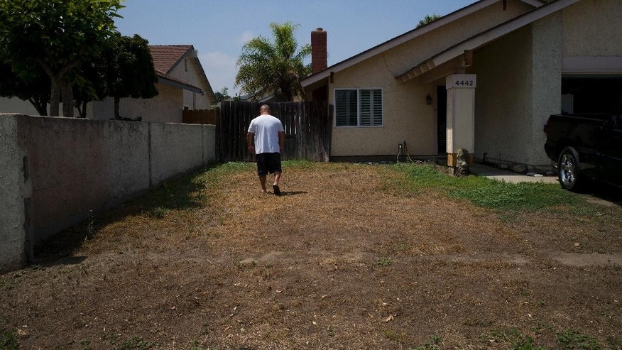 Louis Torres walks though his front yard, left unlandscaped to keep water use to a minimum, Wednesday, May 18, 2016, in Irvine, Calif. California water officials say they will consider dropping a mandate requiring conservation in the state's fifth year of drought. The State Water Resources Control Board on Wednesday will vote on whether to give local water districts control of setting their own conservation targets. (AP Photo/Jae C. Hong)