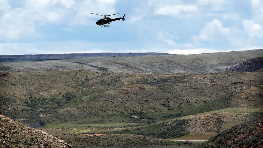 A helicopter circles as law enforcement officials work east of Highway 189 about 16 miles south of Kemmerer, Wyo., Wednesday, May 18, 2016. Law enforcement officials are looking for a possible connection between a missing Utah Transit Authority worker, whose body was discovered late Tuesday evening, and the Centerville, Utah, kidnapping suspects arrested over the weekend.  (Ravell Call/The Deseret News via AP)  SALT LAKE TRIBUNE OUT; MAGS OUT; MANDATORY CREDIT; TV OUT
