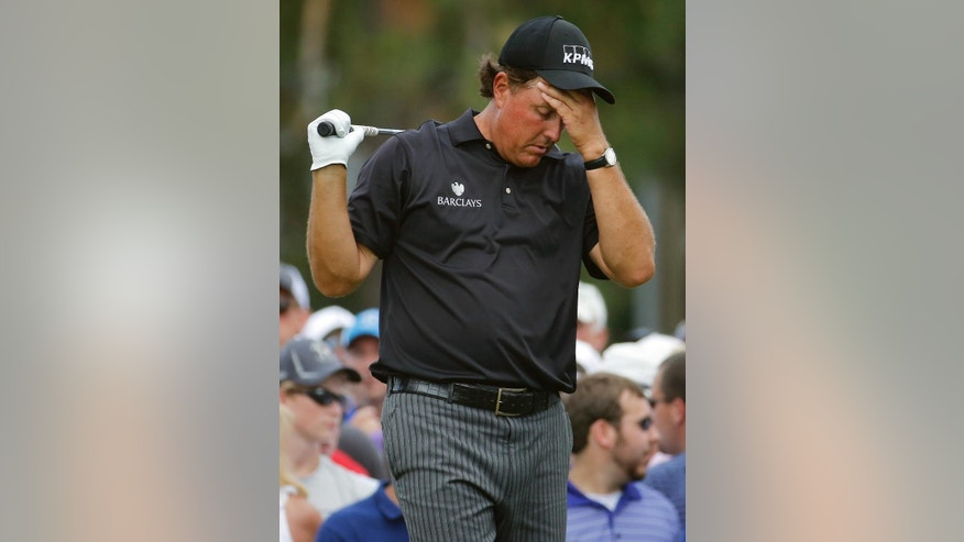 FILE - In this June 12, 2014, file photo, Phil Mickelson, right, reacts to his tee shot on the eighth hole during the first round of the U.S. Open golf tournament in Pinehurst, N.C. The Securities And Exchange Commission is filing a complaint against Mickelson related to insider trading. The SEC says, in 2012 high-profile sports bettor Billy Walters called Mickelson, who owed him money, and urged him to trade Dean Foods stock. The SEC says Mickelson did so the next day and made a profit of $931,000.  The SEC says Walters received tips and business information about Dean Foods Co. from former Dean Foods director Thomas Davis between 2008 and 2012. (AP Photo/Matt York, File)