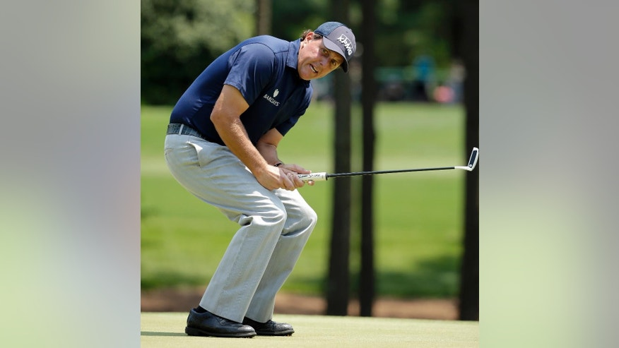 FILE - In this May 7, 2016, file photo, Phil Mickelson reacts as he misses a putt on the third hole during the third round of the Wells Fargo Championship golf tournament at Quail Hollow Club in Charlotte, N.C. The Securities And Exchange Commission is filing a complaint against Mickelson related to insider trading. The SEC says, in 2012 high-profile sports bettor Billy Walters called Mickelson, who owed him money, and urged him to trade Dean Foods stock. The SEC says Mickelson did so the next day and made a profit of $931,000.  The SEC says Walters received tips and business information about Dean Foods Co. from former Dean Foods director Thomas Davis between 2008 and 2012.  (AP Photo/Chuck Burton, File)